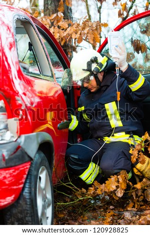 Accident - Fire brigade rescues accident Victim of a car, firefighter holds a drip for Infusion - stock photo