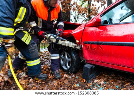 Accident - Fire brigade rescues accident Victim of a car using a hydraulic rescue tool - stock photo