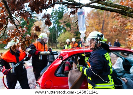 Accident - Fire brigade rescues accident Victim of a car using a hydraulic rescue tool and giving a first aid infusion - stock photo