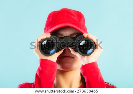 Accident prevention and water rescue. Closeup girl in red lifeguard outfit on duty looking through binocular on blue - stock photo
