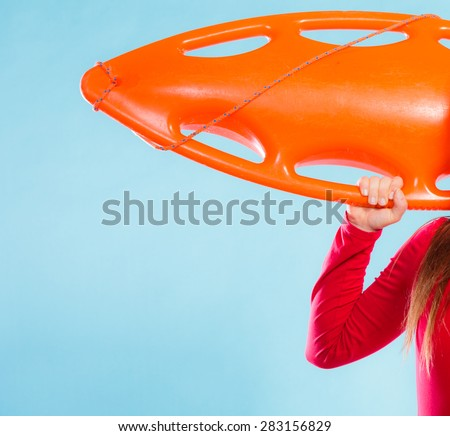 Accident prevention and water rescue. woman female lifeguard on duty holding orange float lifesaver equipment in hand on blue, copyspace - stock photo