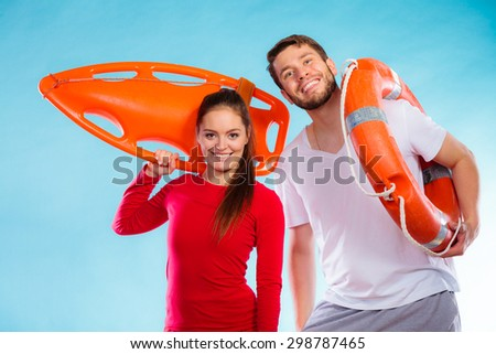 Accident prevention and water rescue. Young man and woman lifeguard couple on duty holding buoy lifesaver equipment on blue - stock photo