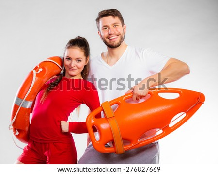 Accident prevention and water rescue. Young man and woman lifeguard couple on duty holding ring buoy float lifesaver equipment on blue - stock photo