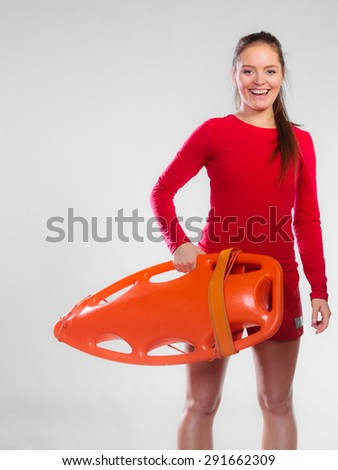 Accident prevention and water rescue. Young woman female smiling lifeguard on duty holding float lifesaver equipment on gray - stock photo