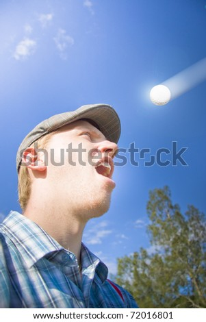Accident Prone Man Stands Shocked And Stunned Watching A Flying Golf Ball Shoot Directly Towards His Head In A Golf Ball Crash Course Collision - stock photo