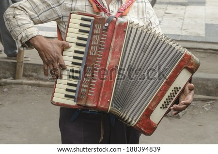 Accordion Man Close view of a street musician playing melodies with his old accordion  - stock photo