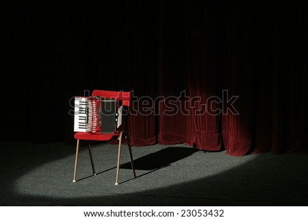 accordion on stage, lighted with a spot light, velvet curtain in background