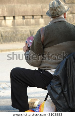 Accordion player on the street playing for change - stock photo