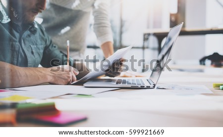 Account manager working process.Young coworkers work with new startup project in office.Analyze document, plans.Modern laptop on wood table, papers, documents.Horizontal, blurred, flare