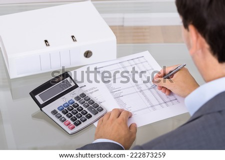 Accountant calculating finances. Over the shoulder view - stock photo