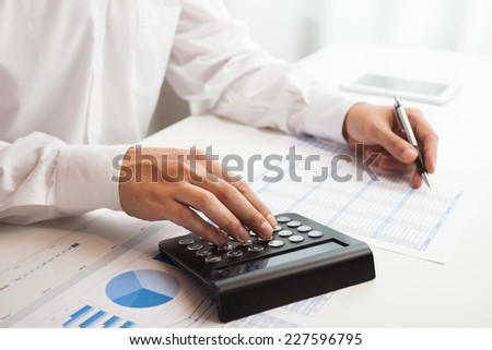 Accountant checking numbers on a document - stock photo