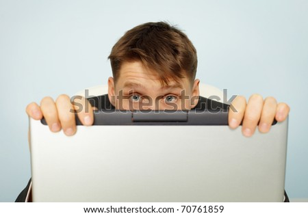 Accountant fear a tax audit - hiding behind a computer - stock photo