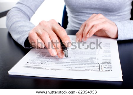 Accountant filling the documents out. - stock photo
