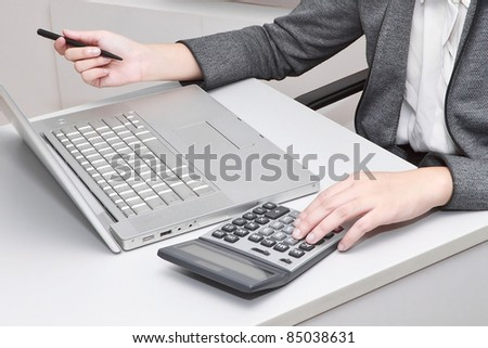 Accountant hand holding pen and pressing calculator buttons