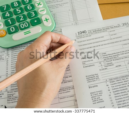 accountant hands using pencil  and tax form - stock photo