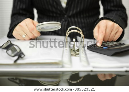 accountant is examining  invoices and documents - stock photo