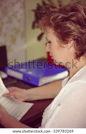 Accountant is reading document and considers on the calculator sitting at her workplace. Vintage style - stock photo