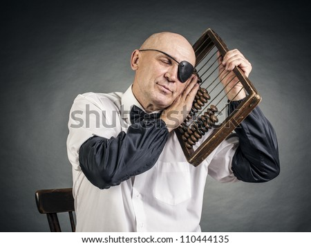 accountant one-eyed and a old abacus - stock photo