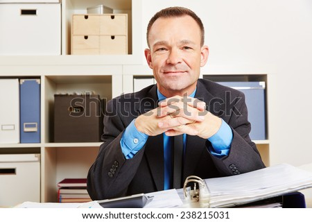 Accountant sitting at his desk in the office with files and a calculator - stock photo