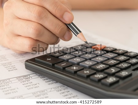 Accountant using a calculator to calculate the numbers. Concept of Savings, Finances and Accounting. - stock photo