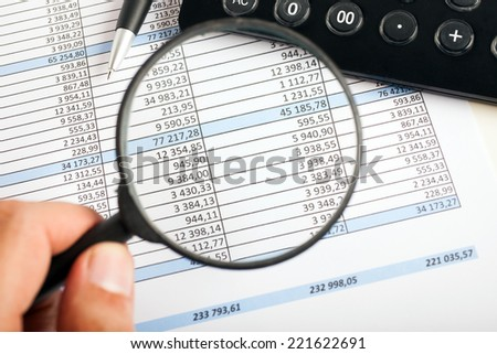 Accountant using a magnifying glass over a business document