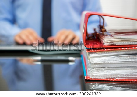 accountant with stack of invoices is inserting data into computer database - stock photo