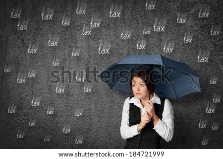 Accountant woman has fear of the tax. Worried businesswoman hide under umbrella against raining tax. - stock photo