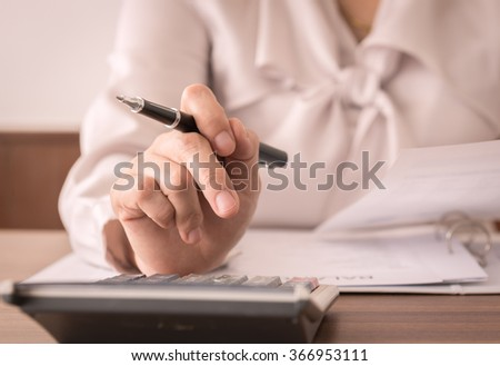 Accountant women or auditor using calculator for check the numbers on the balance sheet. Concept of accounting, bookkeeping,internal audit. - stock photo