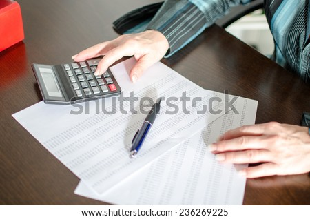Accountant working with calculator at office