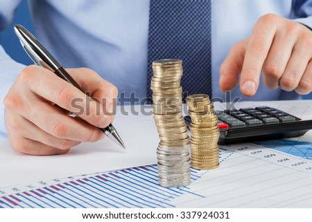Accountants calculating profit - closeup shot of hands counting coins and making notes on paper - stock photo
