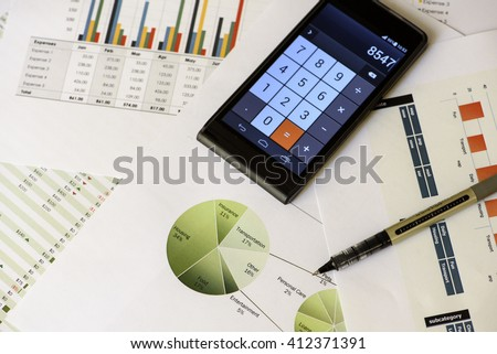 Accounting and personal finance - printed sheets with graphs and pie charts, pen and electronic calculator - income, expenses and totals - stock photo