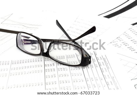 Accounting. black glasses lies on stack document