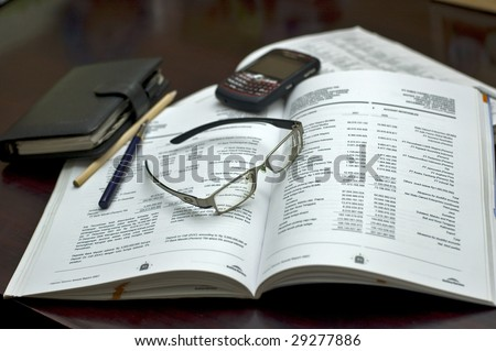 Accounting book, pen, organizer, glasses, PDA and blackberry in the office