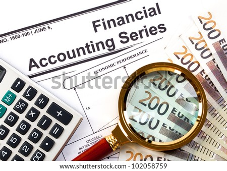 Accounting.Calculator and a magnifying glass is the background of the euro money - stock photo