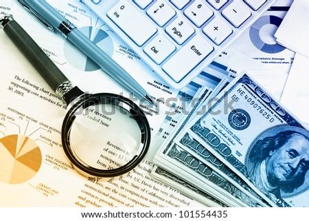 Accounting. Calculator Keyboard and magnifying glass near the money - stock photo