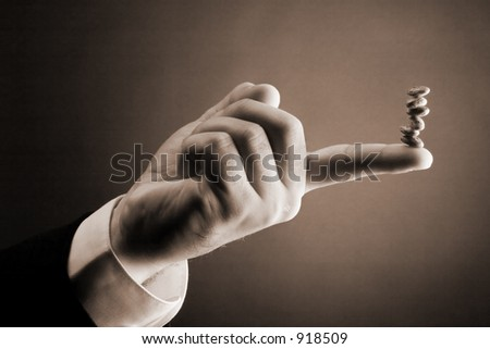 Accounting Concept: Bean Counter: Stack of brown beans balancing on tip of finger. - stock photo