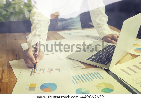 accounting,financial,business man hand working on laptop computer pointing with business graph information diagram on wooden desk,looking serious consultant,lawyer concept,vintage,selective focus - stock photo