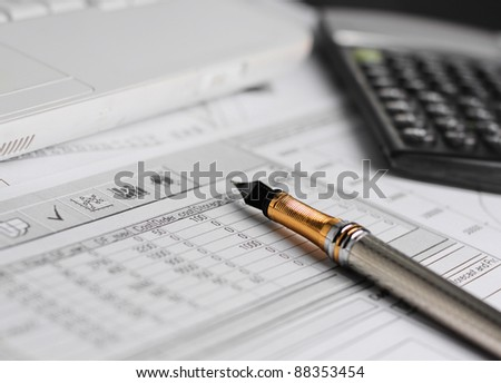 Accounting in process with calculator, pen and financial charts - stock photo