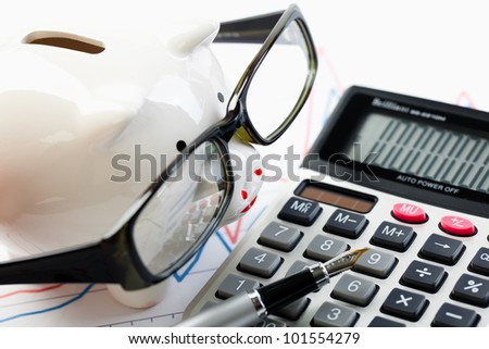 Accounting. Piggy Bank - Pig in glasses near the calculator - stock photo