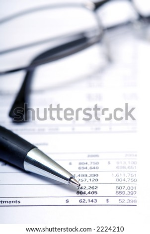 accounting report showing dollar figures with a pen