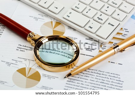 Accounting. The keyboard and pen loop on the background graphics - stock photo