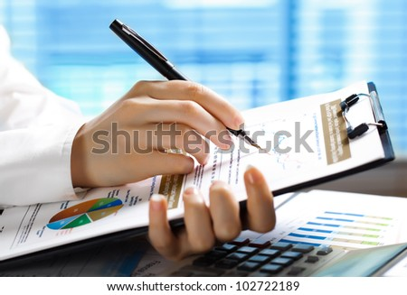 Accounting.Woman's hand with a pen writing on paper - stock photo
