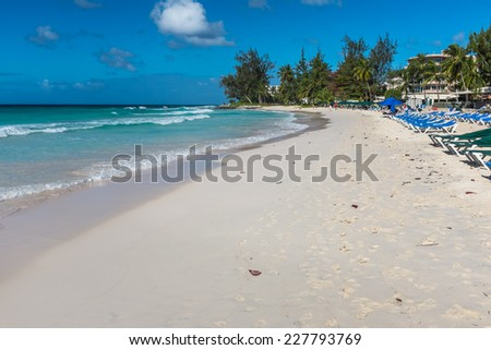 ACCRA BEACH, BARBADOS - FEBRUARY 19, 2014 : Sun loungers and shades lining Accra Beach on the south coast of the Caribbean island of Barbados in the West Indies. Accra is also known as Rockley Beach.