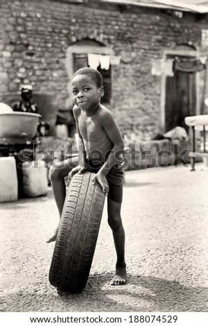 ACCRA, GHANA - MAR 2, 2012: Unidentified Ghanaian little boy play with a tire in the street. Children of Ghana suffer of povert due to the difficult economic situation - stock photo