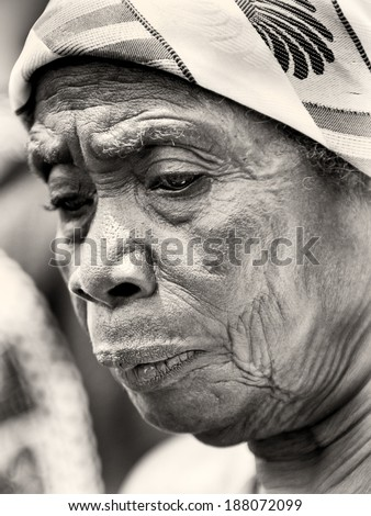 ACCRA, GHANA - MAR 4, 2012: Unidentified Ghanaian old lady in a tissues in the street. People of Ghana suffer of poverty due to the difficult economic situation