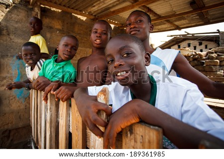 ACCRA, GHANA - MARCH 18: Unidentified african boys greeting to tourists with smiling faces  on May 18, 2014 in Teshie community, Accra, Ghana. Teshie is the famous fishing community in Ghana. - stock photo