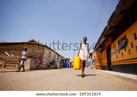 ACCRA, GHANA - MARCH 18: Unidentified african girl walking to carry water back home on May 18, 2014 in Teshie community, Accra, Ghana. Teshie is the famous fishing community in Ghana.