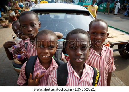 ACCRA, GHANA - MARCH 18: Unidentified african student boys greeting to tourists after school   on May 18, 2014 near Nima, Accra, Ghana. Nima is one of the most deprived community in Ghana. - stock photo