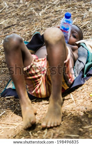 ACCRA, GHANA - MARCH 6, 2012: Unidentified Ghanaian boy takes a rest on the ground in the street in Ghana. Children of Ghana suffer of poverty due to the unstable economic situation