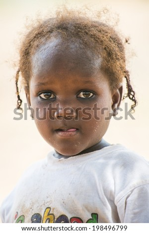 ACCRA, GHANA - MARCH 6, 2012: Unidentified Ghanaian girl in the street in Ghana. Children of Ghana suffer of poverty due to the unstable economic situation